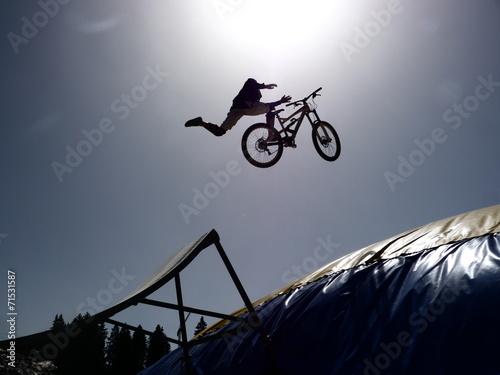 dirtbike bmx rider jumps against sun Canvas Print