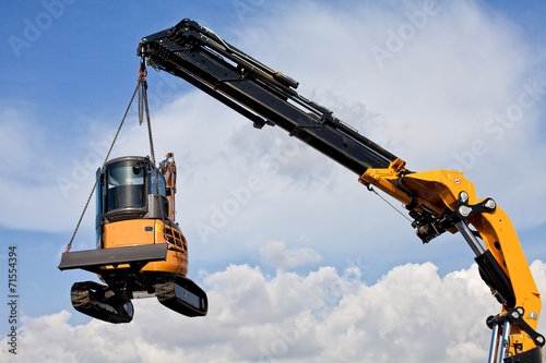 Photo  mini escavatoresollevato da una grù