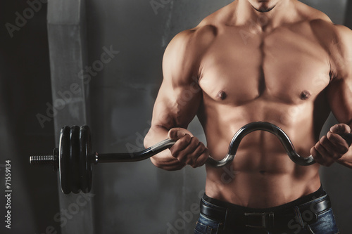 Fotografia Close up of young muscular man lifting weights