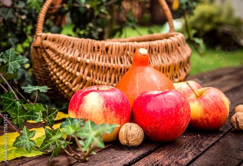 Jesienne warzywa i owoce na drewnianym stole w ogrodzie