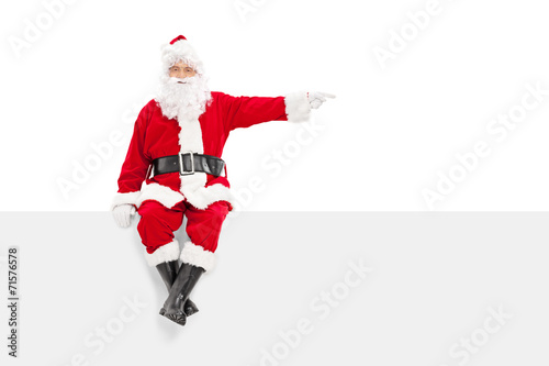 Photo  Santa sitting on a panel and pointing with finger
