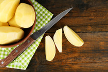 Raw Peeled Potatoes In Bowl  On Wooden Background