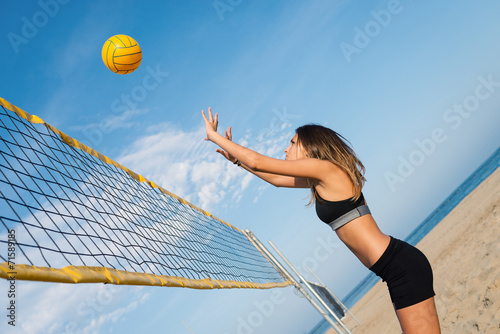 Jumping beach volleyball female player portrait.
