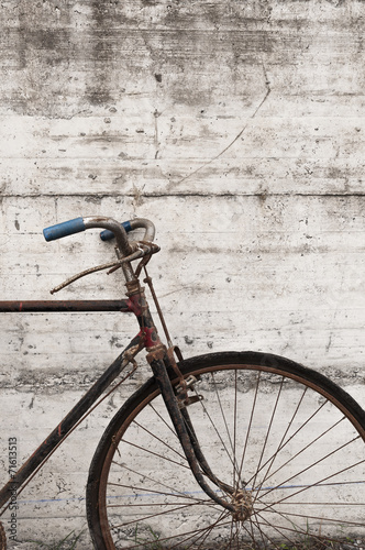 Antique or retro oxidized bicycle outside on a concrete wall