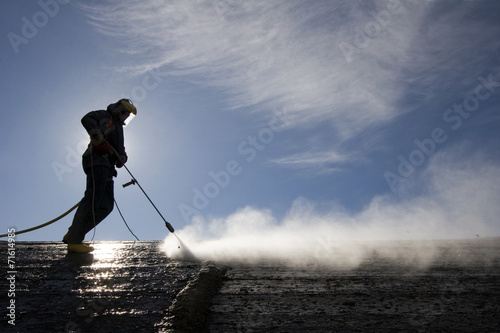 Fotografie, Obraz  Worker on top of factory hall, with high pressure washer
