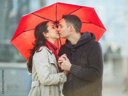 Fotografia  Couple in love under red umbrella.