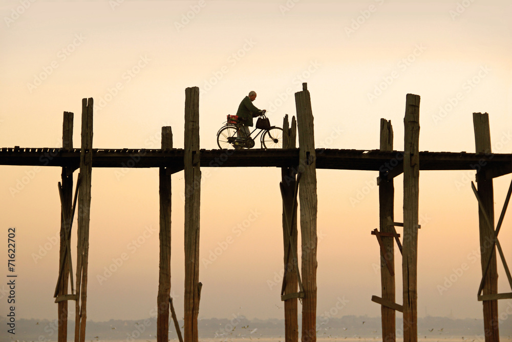Fototapeta cyclist is driving over U Bein's Bridge
