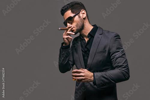 Obraz na plátně  Hard gaze businessman while smoking a cuban cigar