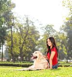 Fototapeta Zwierzęta - Beautiful girl sitting on the grass with her dog