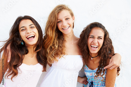 Fotografie, Obraz  Portrait Of Three Teenage Girls Leaning Against Wall