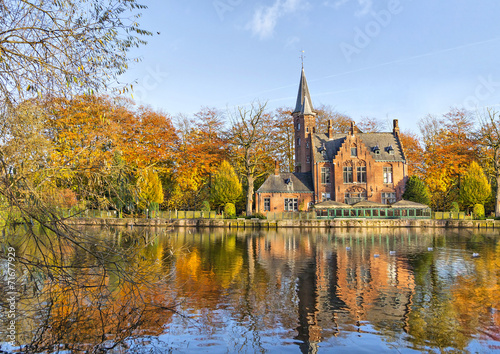 In de dag Brugge Flemish style building reflecting in Minnewater lake, Bruges