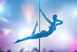 Woman performs pole dance in night club. Sexy body silhouette