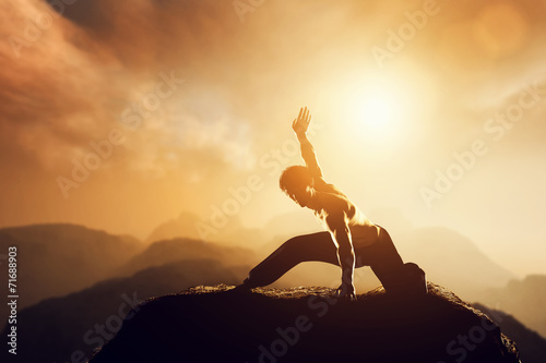 Valokuva Asian man, fighter practices martial arts in mountains. Sunset
