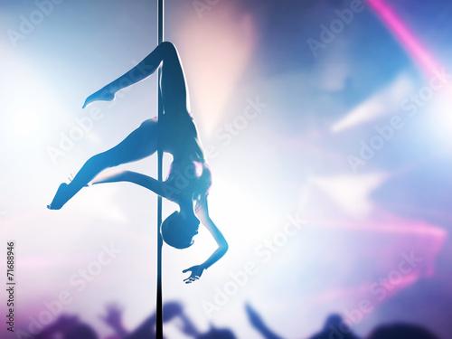 Fotografia  Woman performs pole dance in night club. Sexy body silhouette