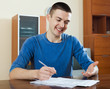 man staring financial documents at table