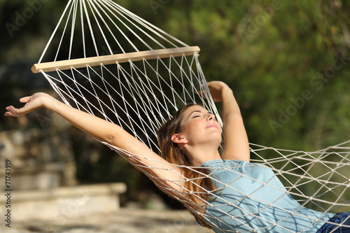 Poster  Happy woman relaxing on a hammock on holidays and raising arms