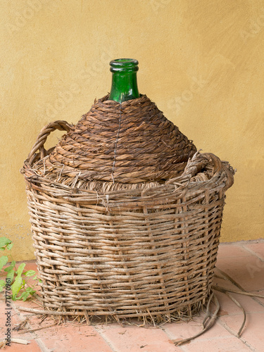 Obraz na plátne Antique old demijohn, carboy, by yellow wall. Wicker basket.