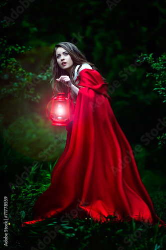 Photo  beautiful woman with red cloak and lantern in the woods