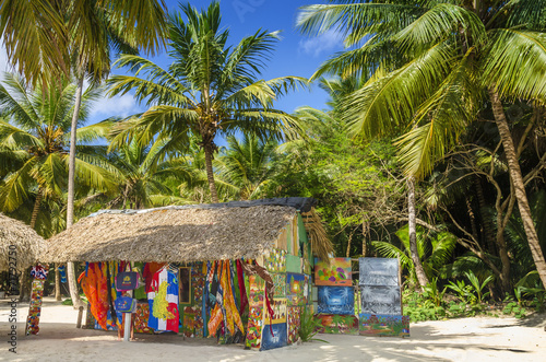 Stampa su Tela Beach with covered with a thatched roof hut with souvenirs