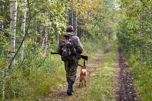 hunter with dog walking on the forest road Poster Mural XXL