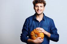Portrait Of A Smiling Man Holding Pumpkin Over Blue Background