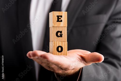 Fotografie, Obraz  Businessman holding wooden alphabet blocks reading - Ego