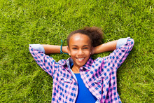 Smiling Beautiful African Girl Laying On Grass