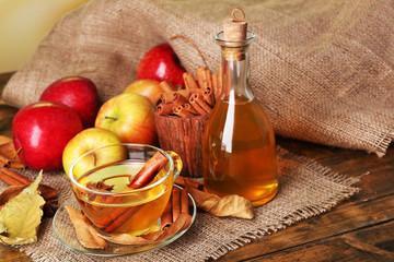 Fototapeta samoprzylepna Composition of apple cider with cinnamon sticks, fresh apples