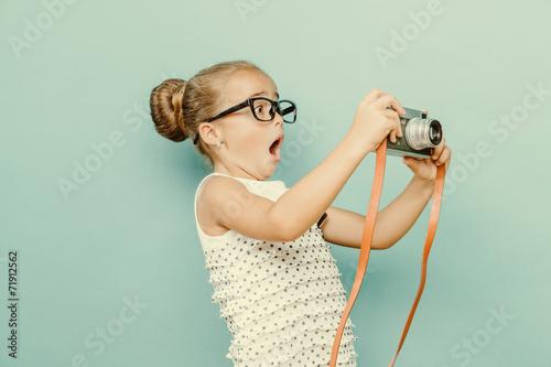 mala-dziewczynka-robiaca-zdjecia-malym-aparatem-na-tle-jasnoniebieskiej-sciany
