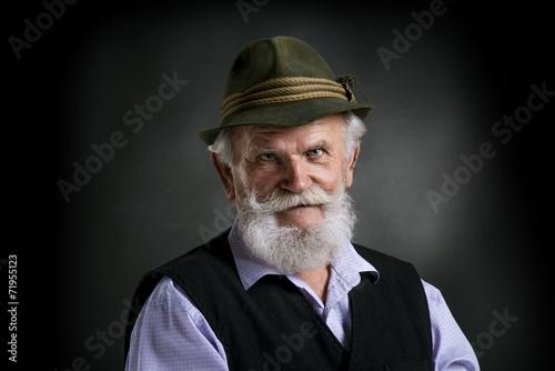 Tableau sur Toile Old bavarian man in hat on black background