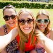 group of smiling teen girls taking selfie in park
