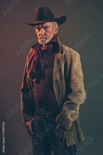 Fotografia, Obraz Old rough western cowboy with gray beard and brown hat. Low key