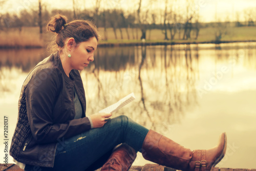 Fototapety, obrazy: Woman reading in sunset at the lake