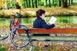 Woman with bicycle sitting in the park and reads