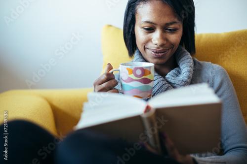 Fotografie, Obraz  Žena pití čaje a čtení knihy na pohovce