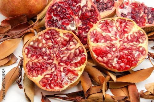 Granadas frescas sobre fondo de hojas secas de otoño Wallpaper Mural
