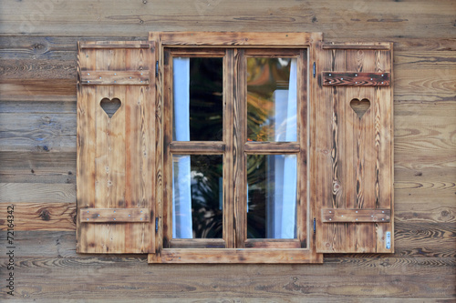 Fotomural Window of a wooden hut with hearts in the blinds