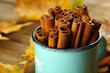 Cinnamon sticks in mug with yellow leaves on wooden background