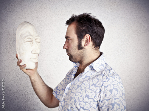 Fotografering  Man looking to a plaster mask