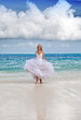 young beautiful woman in dress of the bride runs on waves