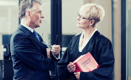 Anwältin mit Gesetzbuch und Mandant Canvas-taulu