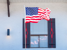 American Flag Reflecting In The Window Of A Storefront