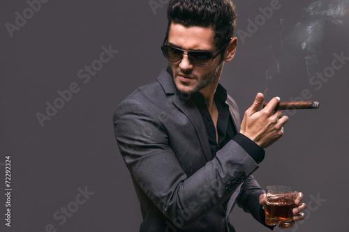 Fotografie, Tablou  Hard gaze businessman while smoking a cuban cigar
