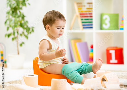 Photo smiling baby sitting on chamber pot with toilet paper