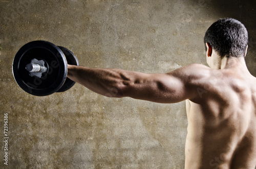 Foto op Plexiglas Fitness Man lifting weights with shoulders training at old gym