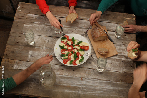 Valokuva  Eating caprese salad with friends, top view