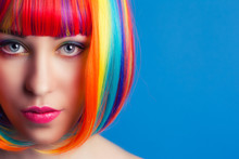 Beautiful Woman Wearing Colorful Wig Against Blue Background
