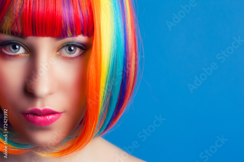 beautiful woman wearing colorful wig against blue background Poster