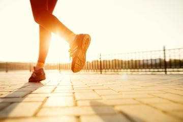 Fototapeta samoprzylepna Runner feet running on road closeup on shoe. woman fitness sunri