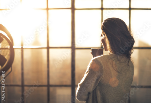 Valokuva  Young woman enjoying cup of coffee in loft apartment. rear view
